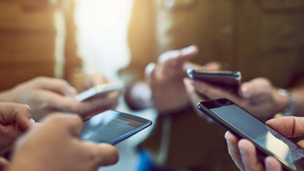 Pessoas a utilizar o smartphone para aceder a sites